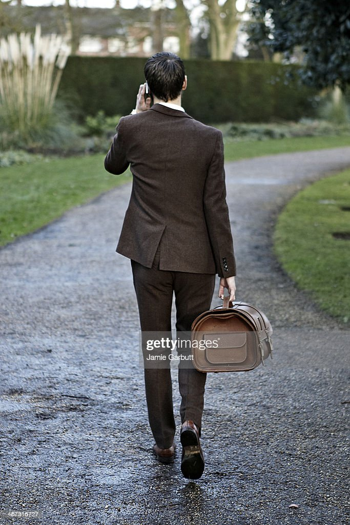 Gentleman walking away from the camera in a park