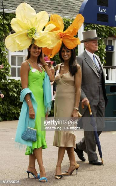 A Gentleman walks past models Jackie St Clair and Kimberley Cowell from London who made their hats out of lampshades for the first day of the Royal...