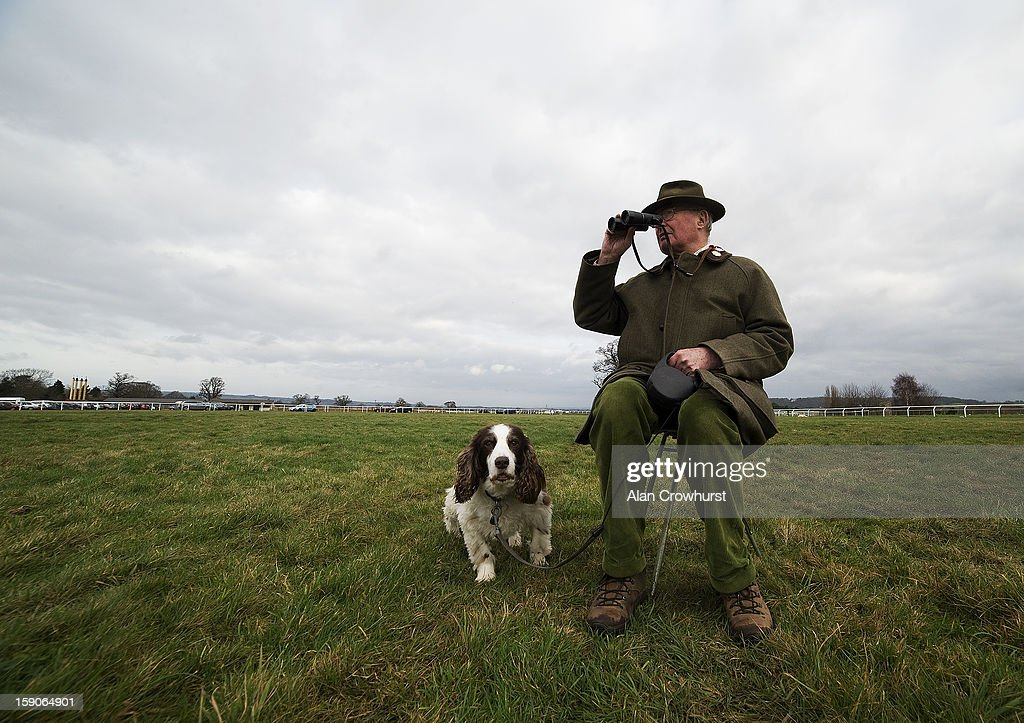 A gentleman watches the action from the centre of the course with his dog Daisy at Taunton racecourse on January 07, 2013 in Taunton, England.
