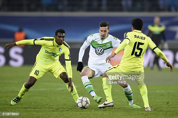 Gent's Brazilian midfielder Renato Neto and Gent's US midfielder Kenneth Saief vie with Wolfsburg's midfielder Julian Draxler during the UEFA...