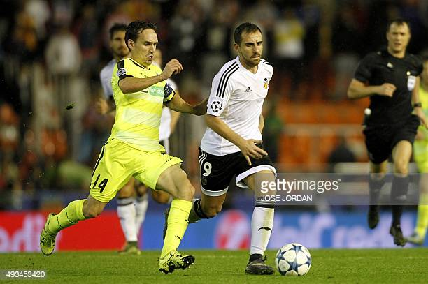 Gent's midfielder Sven Kums vies with Valencia's forward Paco Alcacer during the UEFA Champions League group H football match Valencia CF vs KAA Gent...