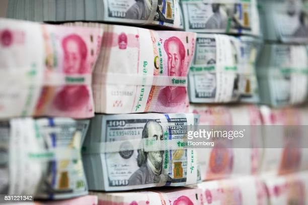 Genuine bundles of Chinese onehundred yuan banknotes and US onehundred dollar banknotes are arranged for a photograph at the Counterfeit Notes...