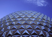 The abstract patterns and colors of a geodesic dome under a blue sky with a slight puff of cloud present.