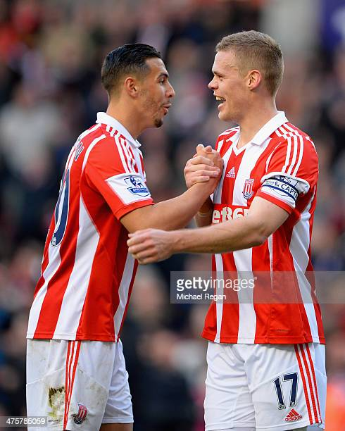 Geoff Cameron of Stoke City celebrates with teammate Ryan Shawcross at the end of the Barclays Pemier League match between Stoke City and Arsenal at...