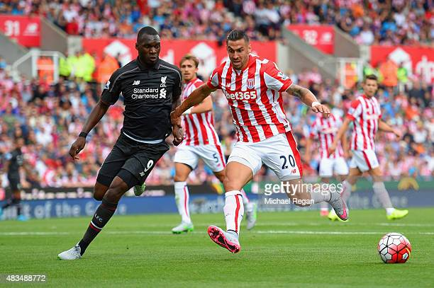 Geoff Cameron of Stoke City holds off Christian Benteke of Liverpool during the Barclays Premier League match between Stoke City and Liverpool at...