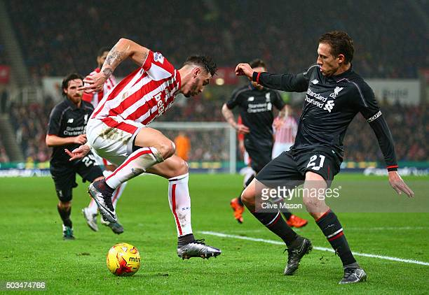 Geoff Cameron of Stoke City is challenged by Lucas Leiva of Liverpool during the Capital One Cup semi final first leg match between Stoke City and...