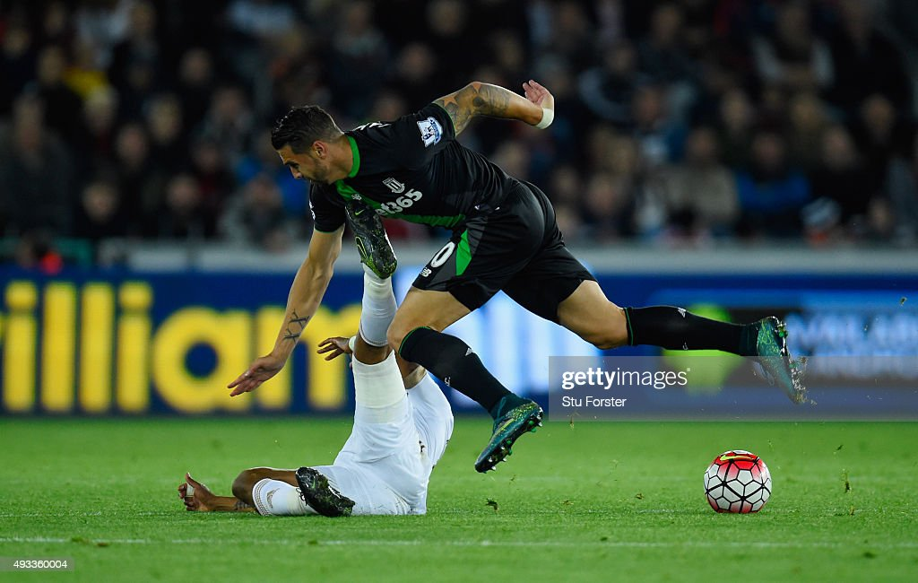 Geoff Cameron of Stoke City is tackled by Andre Ayew of Swansea City during the Barclays Premier League match between Swansea City and Stoke City at Liberty Stadium on October 19, 2015 in Swansea, Wales.