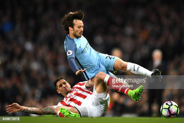 Geoff Cameron of Stoke City tackles David Silva of Manchester City during the Premier League match between Manchester City and Stoke City at Etihad...
