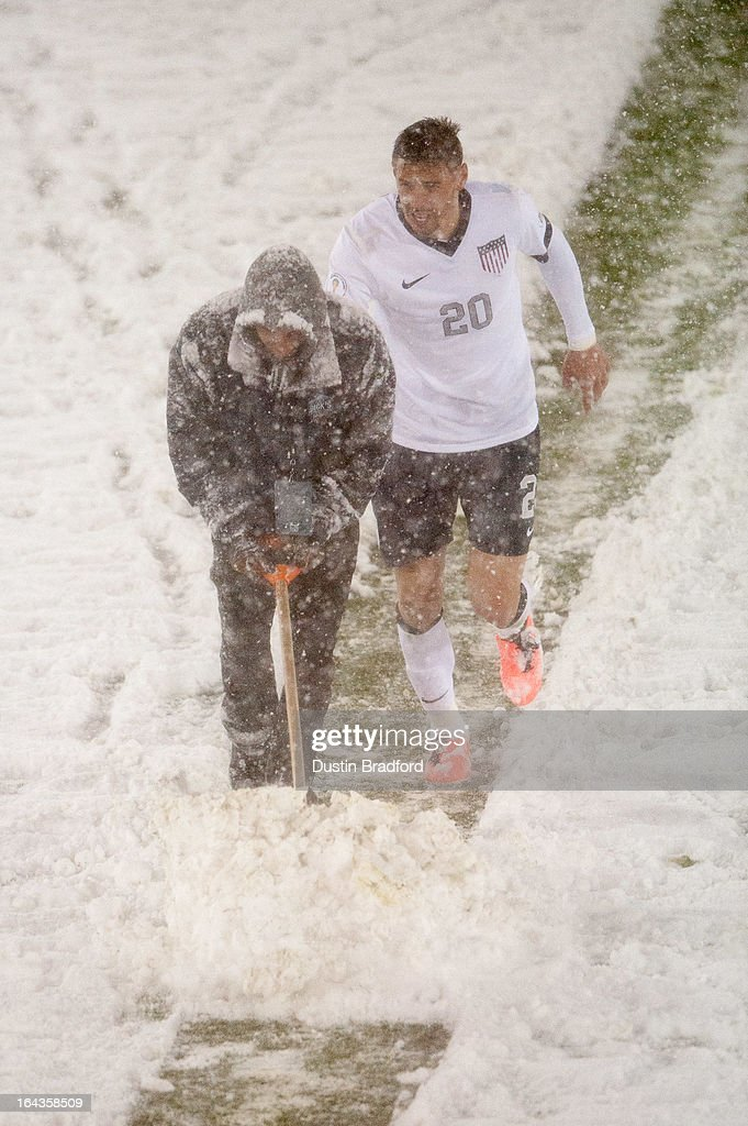 Geoff Cameron of the United States helps push snow by pushing on the back of an event staff person as he clears snow from midfield during a FIFA 2014 World Cup Qualifier match between Costa Rica and United States at Dick's Sporting Goods Park on March 22, 2013 in Commerce City, Colorado.