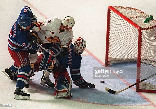 Geoff Courtnall of the Vancouver Canucks slips the puck through the pads of goalie Mike Richter of the New York Rangers as Doug Lidster of the...