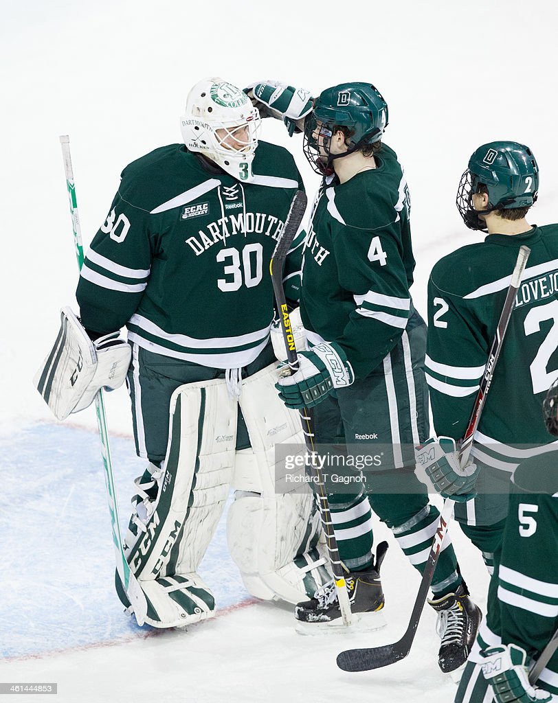 Geoff Ferguson #4 of the Dartmouth College Big Green celebrates a win with <a gi-track='captionPersonalityLinkClicked' href=/galleries/search?phrase=Charles+Grant&family=editorial&specificpeople=749013 ng-click='$event.stopPropagation()'>Charles Grant</a> #30 and Nick Lovejoy #2 after NCAA hockey action against the Boston University Terriers at Agganis Arena on January 8, 2014 in Boston, Massachusetts.