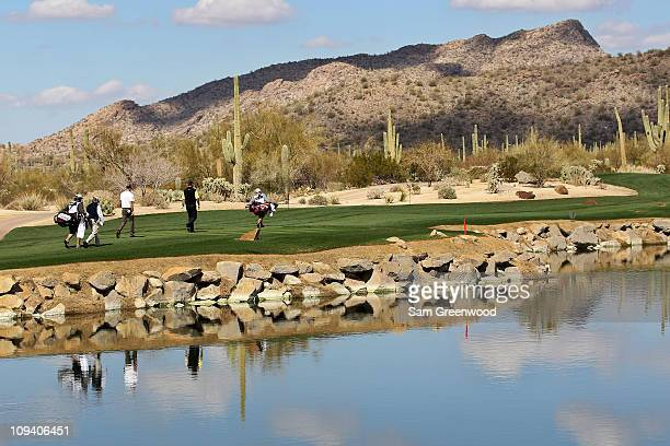 Geoff Ogilvy of Australia and Thomas Bjorn of Denmark walk down the fourth hole with their caddies during the second round of the Accenture Match...