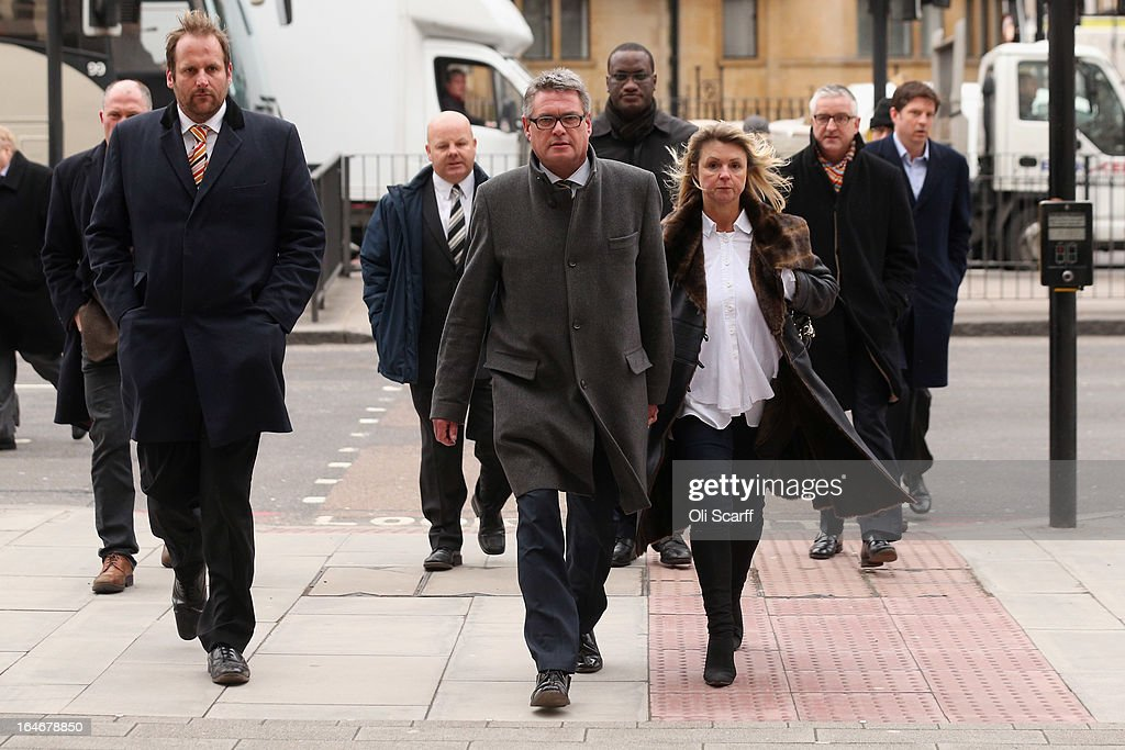 Geoff Webster (C), the deputy editor of the Sun newspaper, arrives at Westminster Magistrates Court with his wife Alison Webster (3rd R) and reporters from the newspaper on March 26, 2013 in London, England. Mr Webster has been charged with allegedly authorising two payments, totaling 8,000 GBP, to public officials for information.