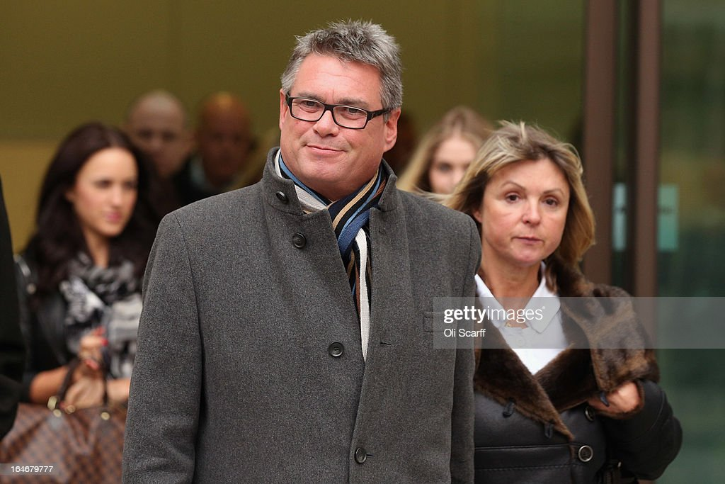 Geoff Webster (C), the deputy editor of the Sun newspaper, leaves Westminster Magistrates Court with his wife Alison Webster (R) on March 26, 2013 in London, England. Mr Webster has been charged with allegedly authorising two payments, totaling 8,000 GBP, to public officials for information.