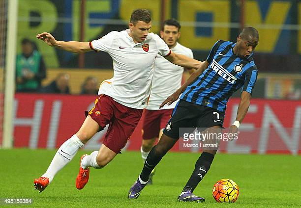 Geoffrey Kondogbia of FC Internazionale Milano is challenged by Edin Dzeko of AS Roma during the Serie A match between FC Internazionale Milano and...