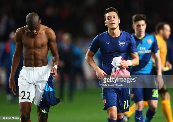 Geoffrey Kondogbia of Monaco and Mesut Oezil of Arsenal swaps shirts at half time during the UEFA Champions League round of 16 second leg match...
