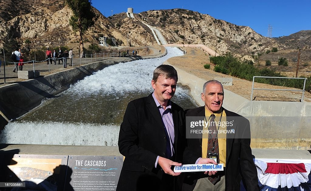 Geoffrey McQuilkin of the Mono Lake Committee and Los Angeles Aqueduct Manager James Yannotta pose while holding a bumper-sticker which says 'I Save Water for Mono Lake' following a re-enactment of the moment the Los Angeles Aqueduct gates were first opened 100 years ago, on November 5, 2013 in Sylmar, California, sending water gushing towards the city during an event marking the 100th anniversary of the opening of the 233-mile Los Angeles Aqueduct, which transports water from the Owens Valley to Los Angeles. The aqueduct started bringing water from the Owens River on the eastern slope of the Sierra Mountains to Los Angeles in November 1913 and the massive public works project is widely credited with transforming Los Angeles from a sleepy agricultural town into a modern metropolis, allowing for the city's rapid expansion. AFP PHOTO/Frederic J. BROWN
