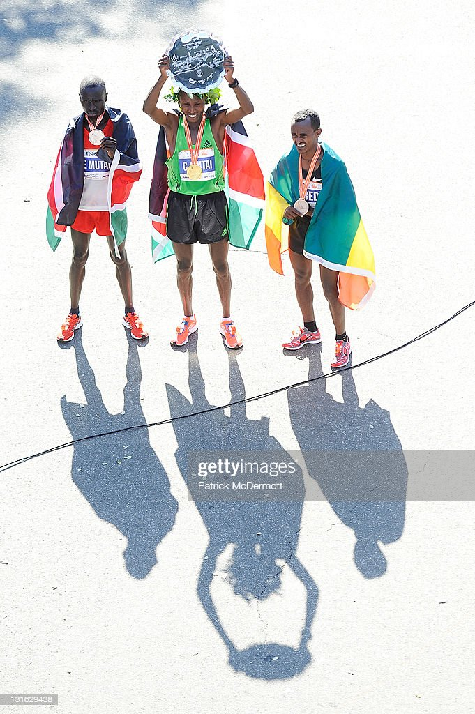 Geoffrey Mutai of Kenya (C), Emmanuel Mutai of Kenya (L), and Tsegaye Kebede of Ethiopia (R) celebrate after the 42nd ING New York City Marathon in Central Park on November 6, 2011 in New York City.