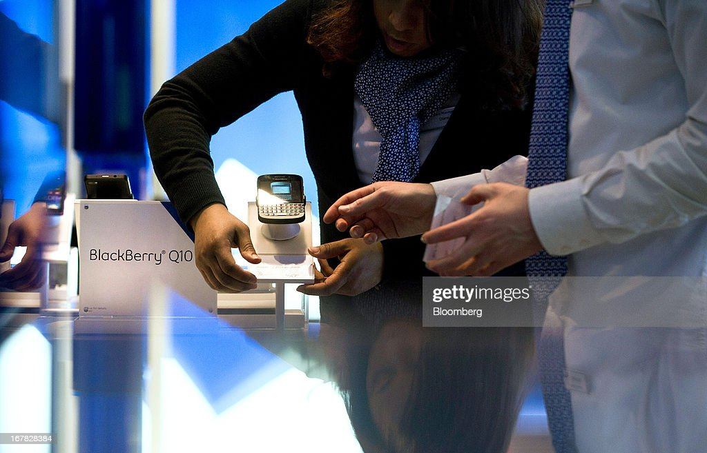 Geoffrey Newsome, sales consultant, right, and Diane Baxter, corporate store manager, prepare a BlackBerry Q10 for display at a Bell Canada retail location in Toronto, Canada, on Tuesday, April 30, 2013. BlackBerry, the Canadian smartphone maker, climbed to its highest level in more than a month after Chief Executive Officer Thorsten Heins said he sees sales of its new Q10 device to be in the 'tens of millions.' Photographer: Galit Rodan/Bloomberg via Getty Images