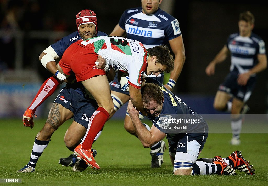 Geoffrey Sella of Biarritz Olympique is tackled by Henry Thomas and Sam Tuitupou of Sale during the Amlin Challenge Cup match between Sale Sharks and...