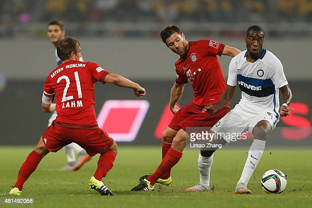 Geoffry Kongdogbia of FC Internazionale challenges Xabi Alonso and Philipp Lahm of FC Bayern Muenchen during the international friendly match between...