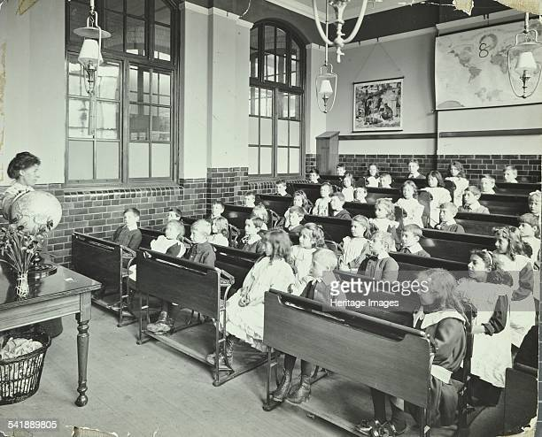 Geography lesson Denmark Hill School Dulwich London 1905 A teacher uses a globe to instruct an attentive class of young children Artist unknown