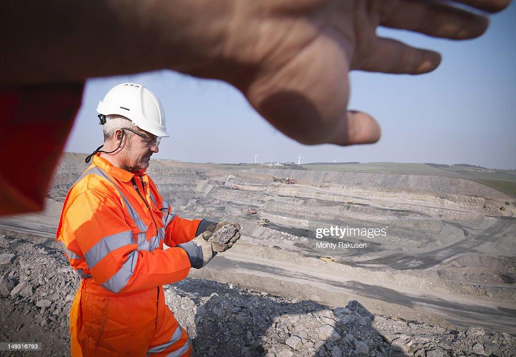 Geologist inspecting rock in opencast coalmine : Stock Photo