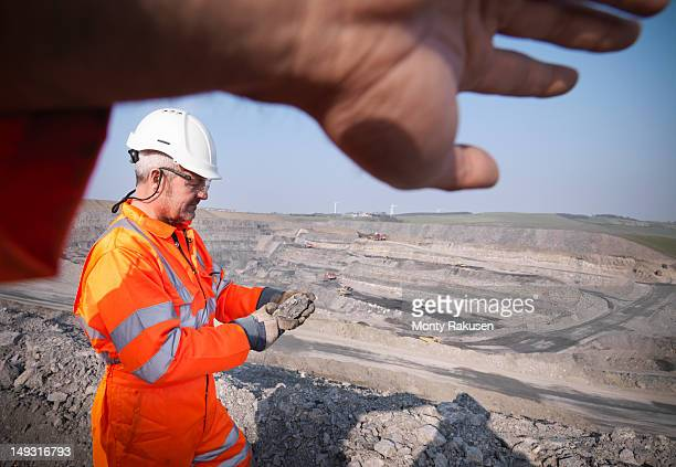 Geologist inspecting rock in opencast coalmine