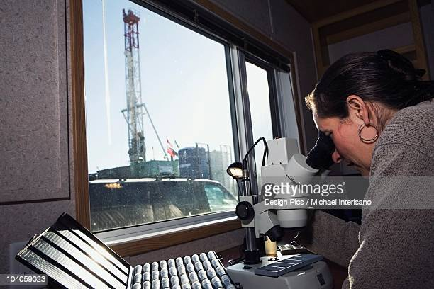 Geologist Looking Into A Microscope At Samples On A Rig Site
