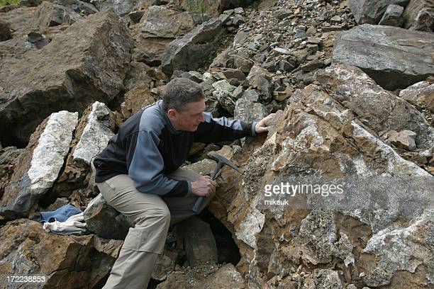Geologist scientist man looking at rock in quarry