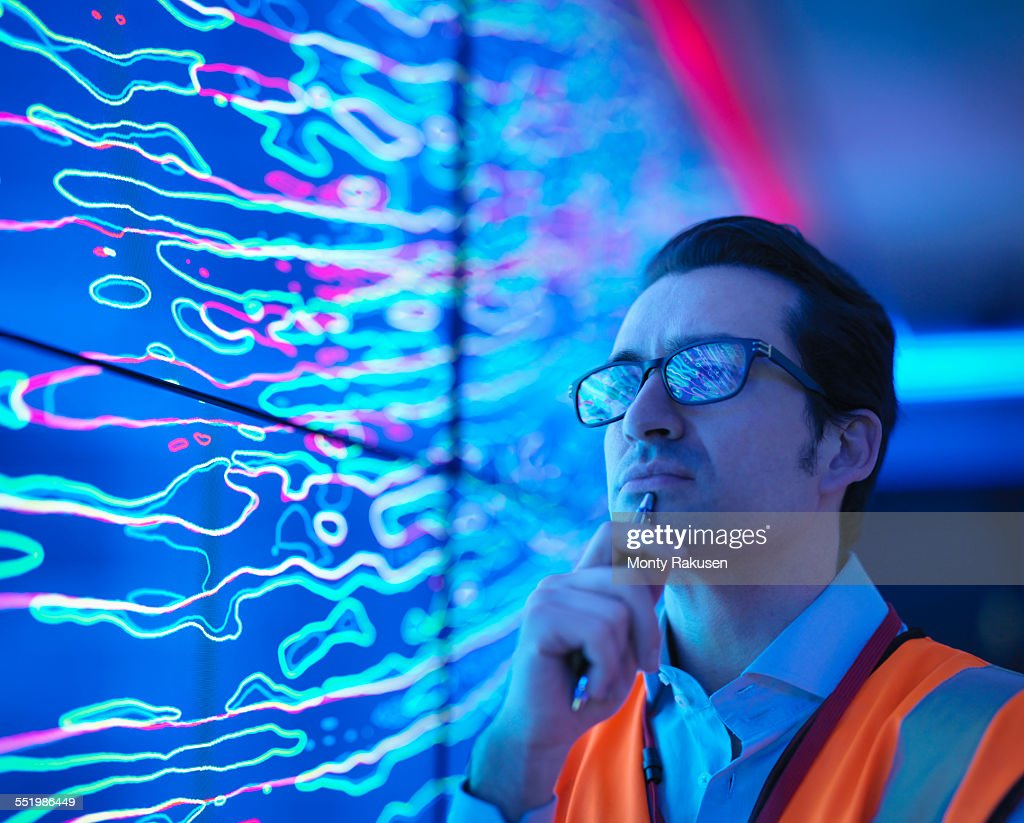 Geologist studying graphical display of oil and gas bearing rock on screens, close up