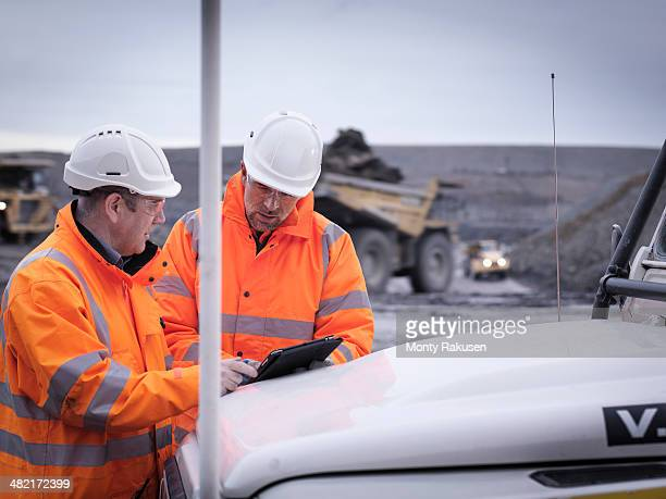 Geologists discuss plans on digital tablet in surface coal mine