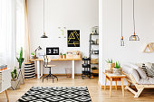 Black and white geometric carpet in multifuncional workspace with painting on wall above desk