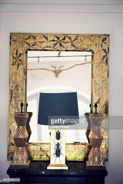 A geometric mirror with a pattern taken from a 19thcentury Japanese kimono is fronted by a trio of Tennant and Tennant lamps Photographed for the New...