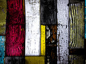 Background of painted wood effect showing vibrant colours, pinks, yellows, whites, brown and greys. taken to look like a stained glass effect