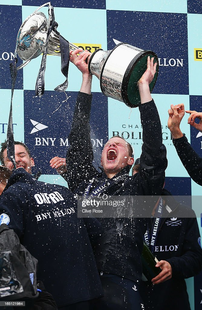 Geordie Macleod of Oxford lifts the trophy as team mates celebrate after the BNY Mellon 159th Oxford versus Cambridge University Boat Race on The River Thames on March 31, 2013 in London, England.