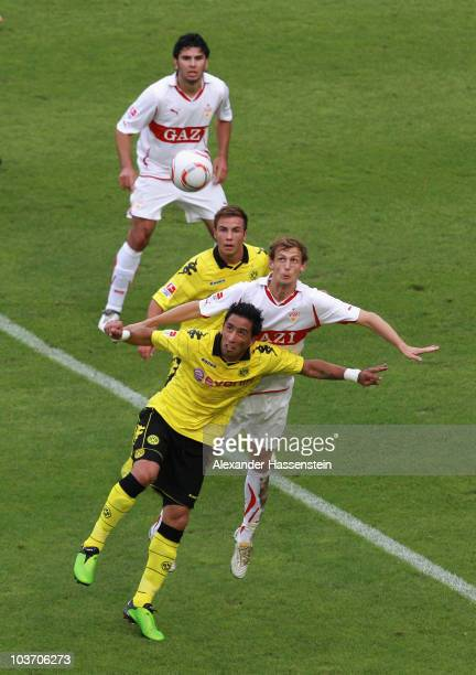 Georg Niedermeier of Stuttgart battles for the ball with Lucas barrios of Dortmund and his team mate Mario Goetze whilst Serdar Tasci of Dortmund...