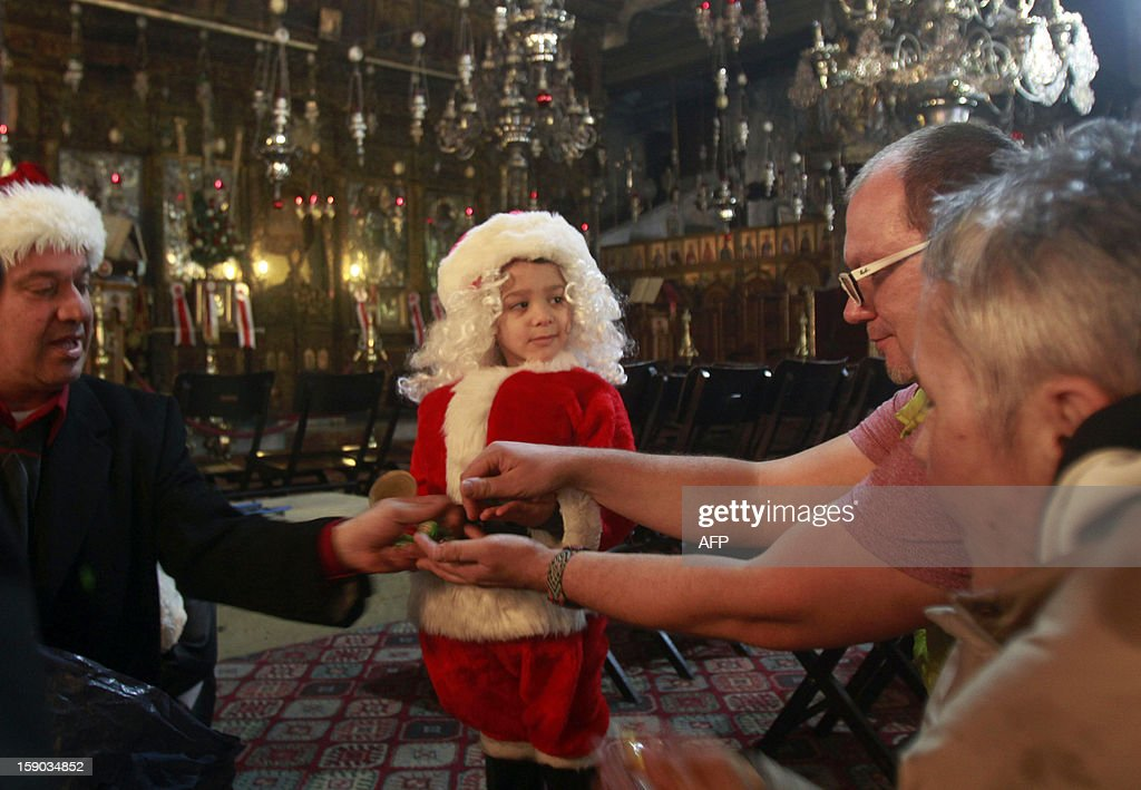 George, a Palestinian Christian boy, dressed up as Santa Claus, shares sweets in the Church of the Nativity, accepted by Christians as the birth place of Jesus Christ, as faithful flock to the church to celebrate Christian Orthodox Christmas eve, on January 6, 2013, in the West Bank town of Bethlehem. AFP PHOTO/MUSA AL-SHAER