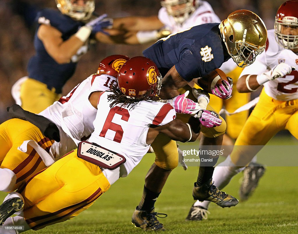 George Atkinson III #4 of the Notre Dame Fighting Irish is hit by Hayes Pullard #10 and Josh Shaw #6 of the University of Southern California Trojans at Notre Dame Stadium on October 19, 2013 in South Bend, Indiana. Notre Dame defeated USC