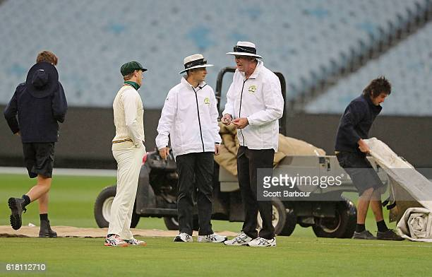 George Bailey captain of Tasmania speaks with umpires Geoff Davidson and Geoff Joshua as the groundsmen put the covers on as the players leave the...
