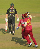 George Bailey of Australia leaves the field as Denesh Ramdin congratulates Darren Sammy of the West Indies for taking the catch during the ICC World...