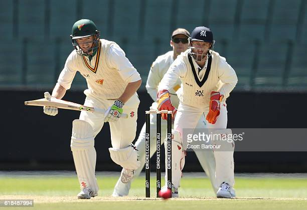 George Bailey of Tasmania bats as wicketkeeper Matthew Wade of Victoria looks on during day three of the Sheffield Shield match between Victoria and...