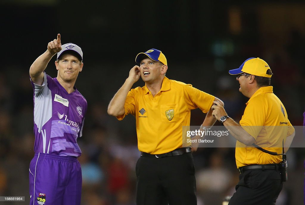 George Bailey of the Hurricanes speaks with umpires Sam Nogajski and John Ward after a ball hit by Aaron Finch of the Renegade hit the roof during the Big Bash League match between the Melbourne Renegades and the Hobart Hurricanes at Etihad Stadium on December 19, 2012 in Melbourne, Australia.
