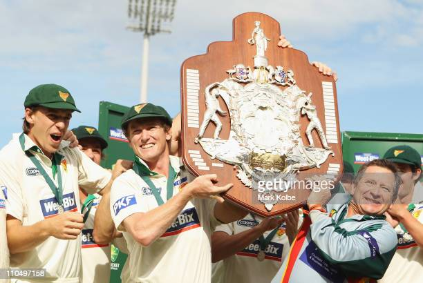 George Bailey of the Tigers and Tigers head coach Tim Coyle lift the Shield Shield after winning on day five of the Sheffield Shield final match...