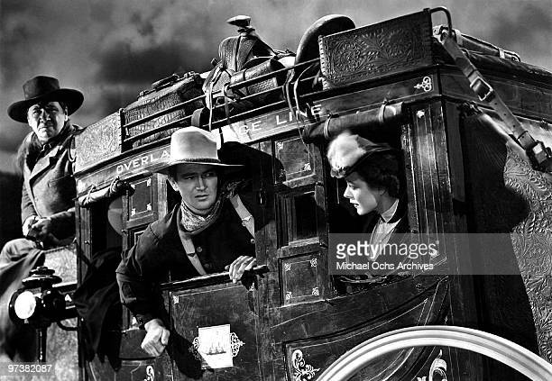 George Bancroft John Wayne and Louise Platt on the set of the movie 'Stagecoach' in 1939