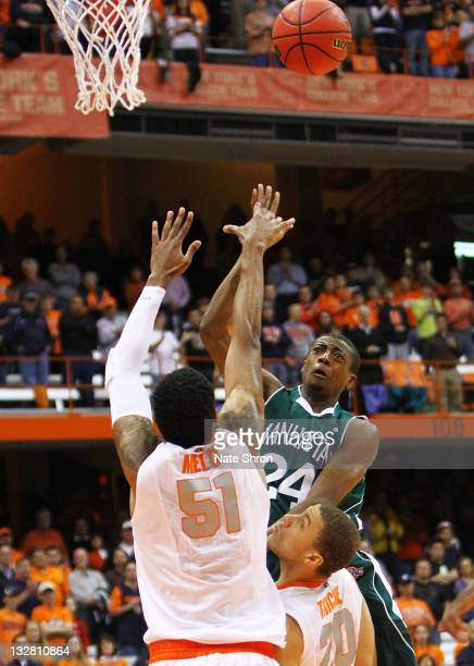 George Beamon of the Manhattan College Jaspers shoots the ball against Fab Melo and Brandon Triche of the Syracuse Orange during the NIT Season...