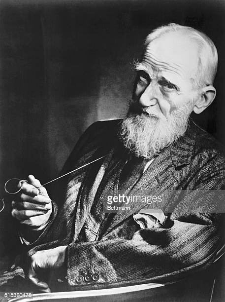 George Bernard Shaw British playwright and critic shown waistup holding his glasses Undated photograph