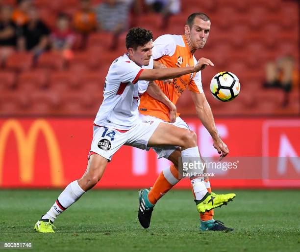 George Blackwood of Adelaide United contests the ball with Corey Brown of the Roar during the round two ALeague match between the Brisbane Roar and...
