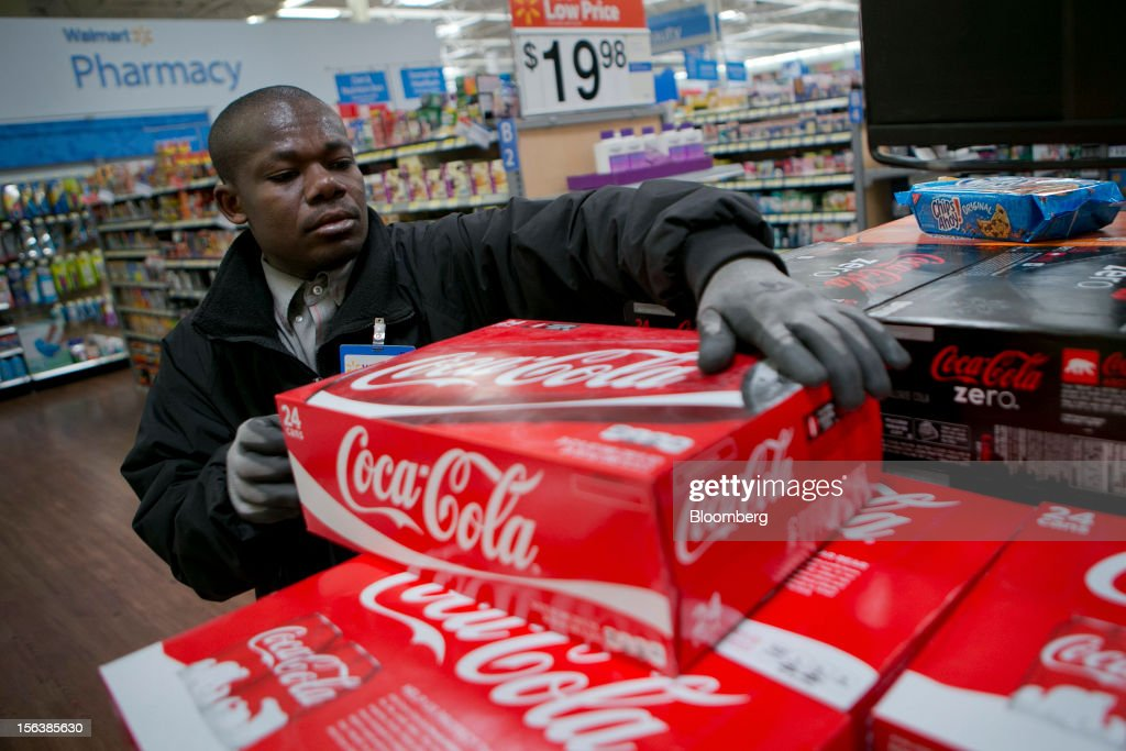 George Boakye stocks Coca-Cola Co. products at a Wal-Mart store in Alexandria, Virginia, U.S., on Wednesday, Nov. 14, 2012. Wal-Mart Stores Inc. is scheduled to release earnings data on Nov. 15. Photographer: Andrew Harrer/Bloomberg via Getty Images