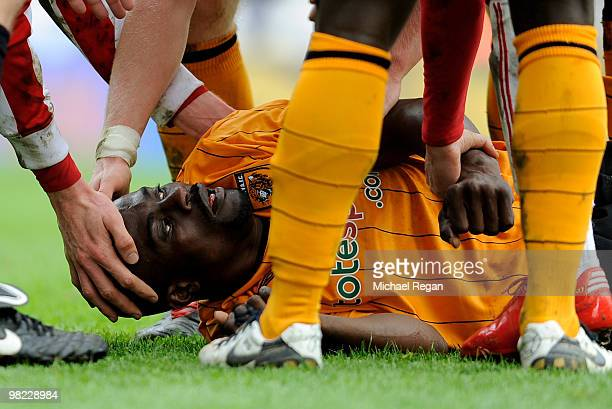 George Boateng of Hull is helped by other players as he lies injured following a kick in the head during the Barclays Premier League match between...